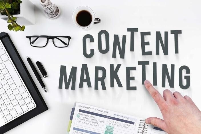 A white desk with the words content marketing written on it and a hand pointing to these words because it is important to know the crucial cornerstone content marketing tips.